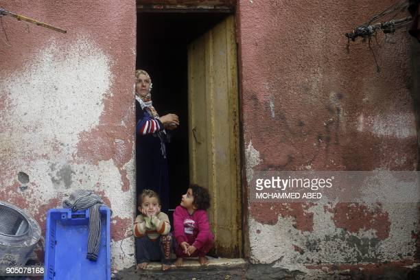 Palestinian woman and her children are seen on the doorstep of their home in Gaza City on January 15 2018 / AFP PHOTO / MOHAMMED ABED