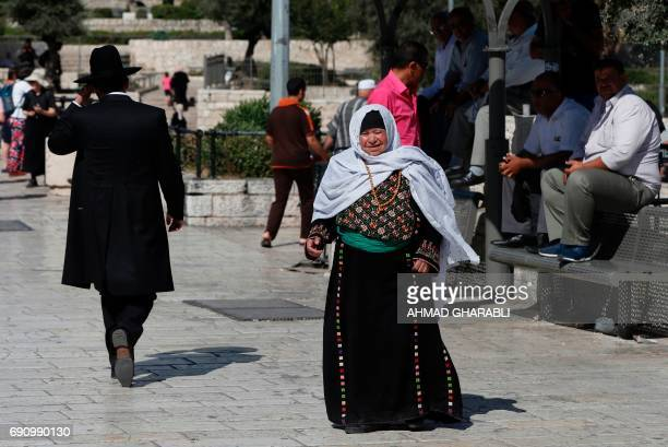 A Palestinian woman and Jewish man walk in east Jerusalem on May 31 2017 Fifty years after Israel seized east Jerusalem in the 1967 SixDay War more...