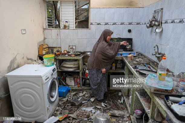 Palestinian woman boils water in the kitchen of her house that was damaged in an Israeli air strike in Jabalia, in the northern Gaza Strip, on May...