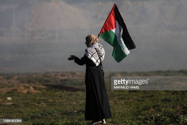 A Palestinian woman carries a national flag during a demonstration along the border with Israel east of Gaza City on January 25 2019 A Palestinian...