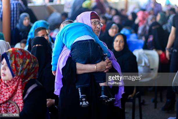 Palestinian woman carries her baby as she hopes to cross into Egypt at the Rafah crossing between Egypt and the southern Gaza Strip April 29, 2014....