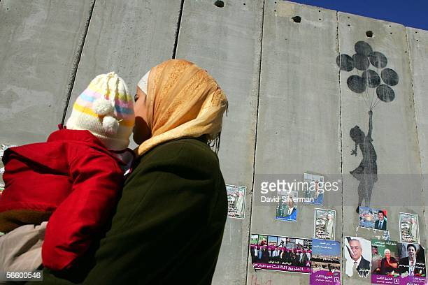 Palestinian woman carries her child past grafitti by the British artist Banksy on Israel's separation wall January 16 2006 near the Israeli army's...