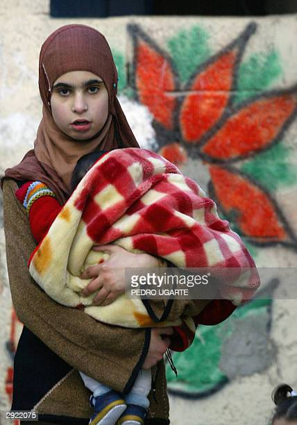 Palestinian woman carries her son at Aida refugee camp on the edge of the West Bank city of Bethlehem 02 February 2004 A member of the Hamas movement...