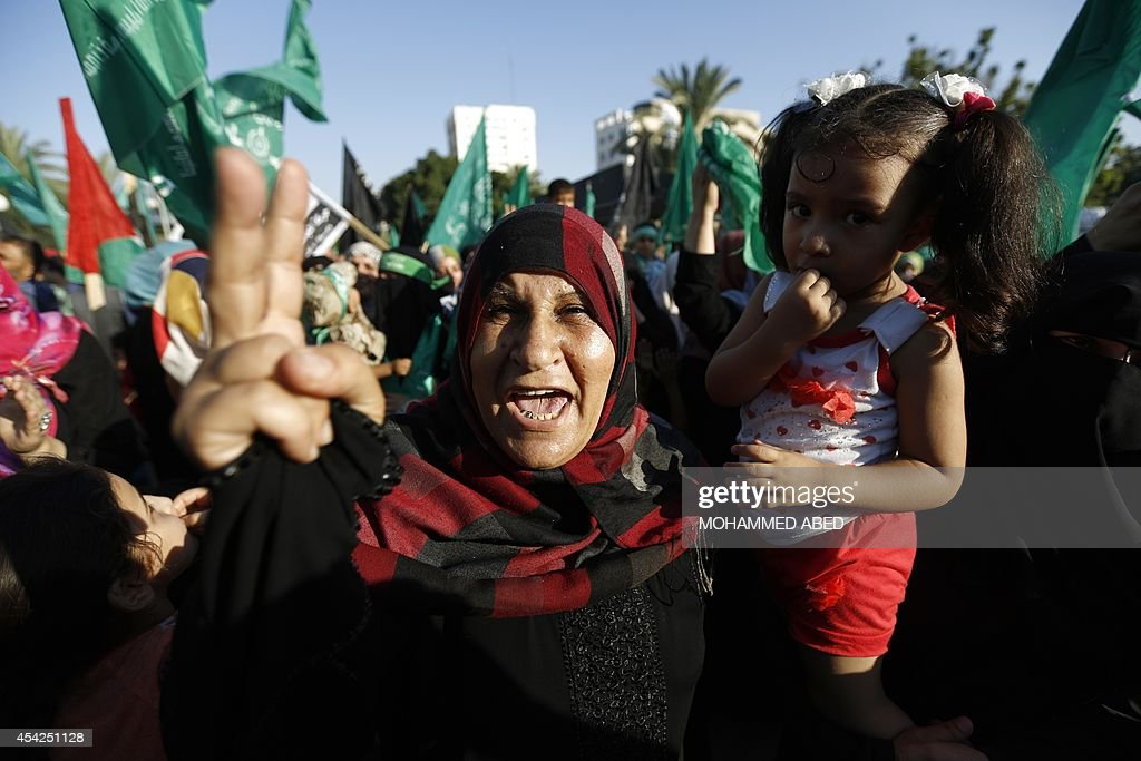 A Palestinian woman carrying a young girl celebrates in Gaza City on August 27, 2014, during a rally following a deal hailed by Israel and the Islamist Hamas movement as 'victory' in the 50-day war. The agreement, effective from 1600 GMT on August 26, saw the warring sides agree to a 'permanent' ceasefire which Israel said would not be limited by time, in a move hailed by Washington, the United Nations and top world diplomats.