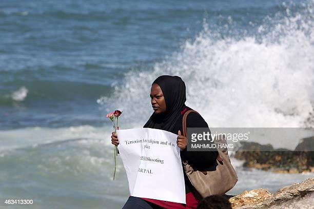 A Palestinian woman carrying flowers gathers at the sea of Gaza City on February 14 in remembrance of the three victims of the Chapel Hill shooting...
