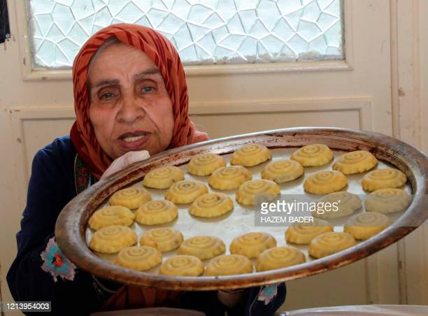 Palestinian woman, clad in gloves due to the COVID-19 coronavirus pandemic, showcases a tray of prepared traditional biscuits ahead of the upcoming...