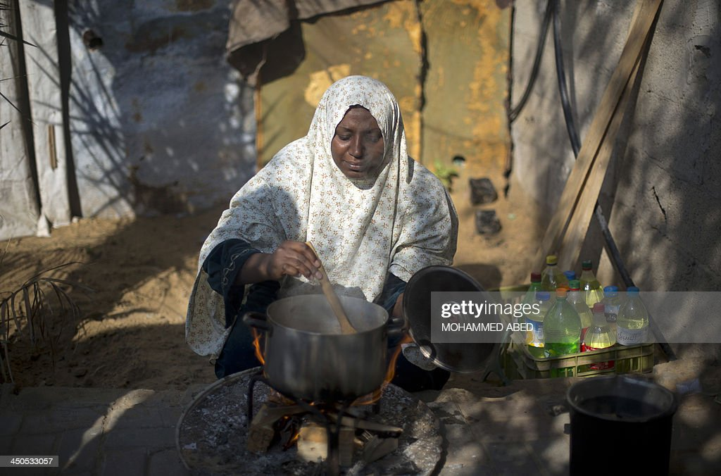 A Palestinian woman cooks her food on fire wood in Biet Hanun northern Gaza Strip, on November 19, 2013, due to the shortage in butane gas across the Hamas run Palestinian territory.