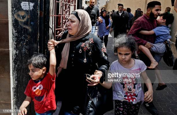 Palestinian woman cries as civilians evacuate a building targeted by Israeli bombardment in Gaza City on May 11, 2021. - Israel launched deadly air...