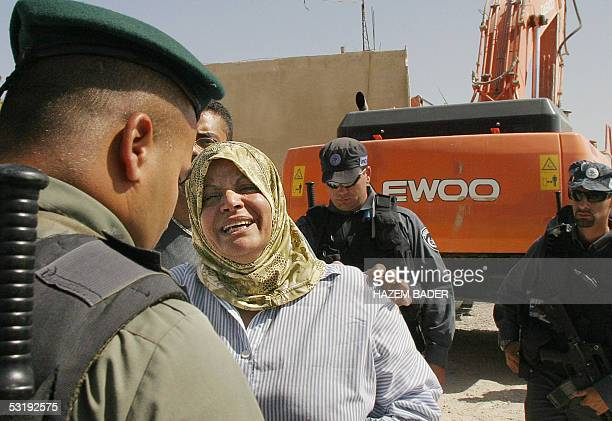 Palestinian woman cries while Israeli border policemen stand guard near a bulldozer demolishing a Palestinian house built without permission in Beit...
