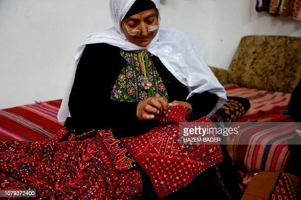 A Palestinian woman cross stitches a traditional Palestinian dress known as 'Thobe' in Idna village near the West Bank town of Hebron on January 8...