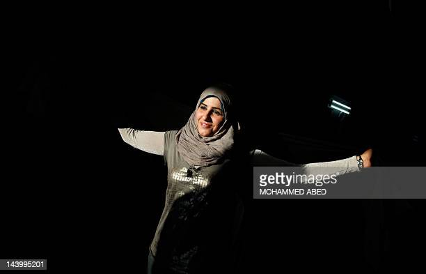 A Palestinian woman dances during a concert by the Egyptian band Iskandarella in Gaza City on May 7 2012 in support of more than a thousand prisoners...