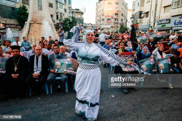 Palestinian woman dances in a square during a demonstration in a square in the West Bank city of Ramallah on September 27 ahead of his speech during...