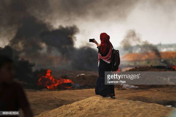 Palestinian woman documents the situation at the border fence with Israel as mass demonstrations continue on May 14 2018 in Gaza City Gaza Israeli...