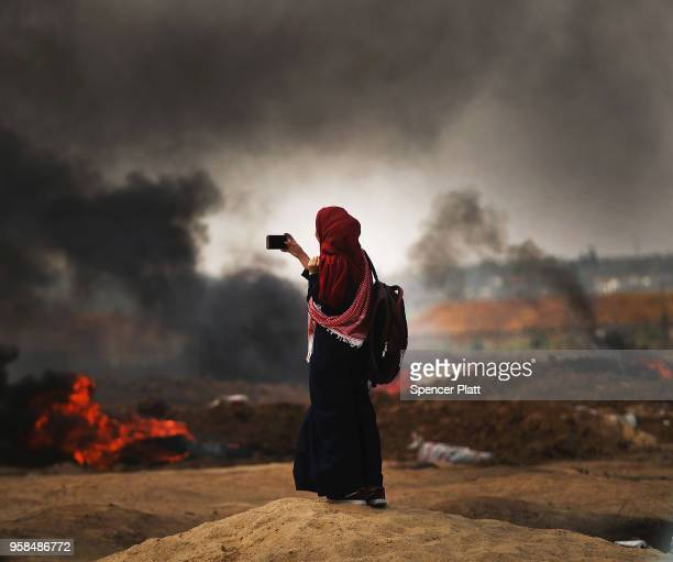 A Palestinian woman documents the situation at the border fence with Israel as mass demonstrations continue on May 14 2018 in Gaza City Gaza Israeli...