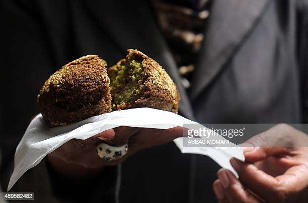 Palestinian woman eats falafel a traditional dish consisting of fried chickpeas on a street in the West Bank city of Nablus on September 19 2015 AFP...