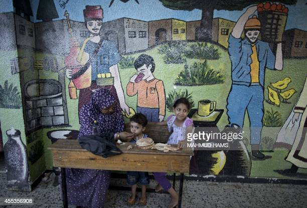 A Palestinian woman feeds her children at a classroom at a United Nationsrun school in Gaza City on September 13 2014 one day before children go back...