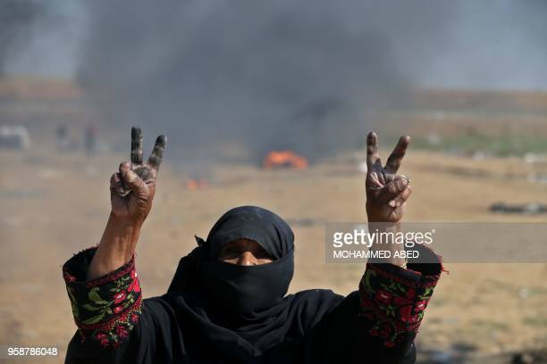 """Palestinian woman flashes the """"V"""" for victory sign during protest near the border fence with Israel east of Jabalia in the central Gaza Strip on May..."""