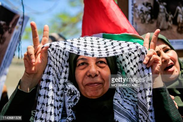 Palestinian woman flashes the victory gesture as she raises her keffiyeh above her head during a demonstration commemorating the 71st anniversary of...