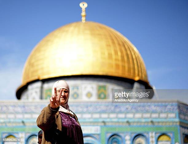 Palestinian woman flashes victory sign in front of Dome of the Rock during Friday prayer as Israeli government has lifted restrictions for the entry...