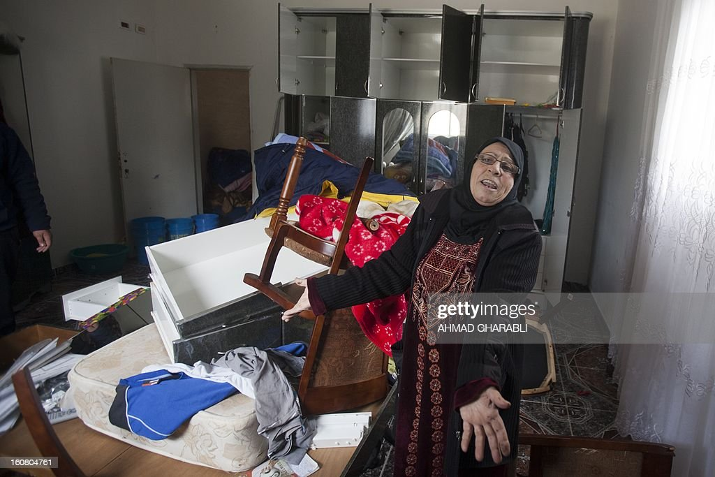 A Palestinian woman from the Siyam family, gestures as she looks at a ransacked room after Israeli soldiers entered her house in East Jerusalem's Arab neighbourhood of Silwan, on February 6, 2013, during a neighborhood search operation for the past couple of days, in which several Palestinians have been arrested.