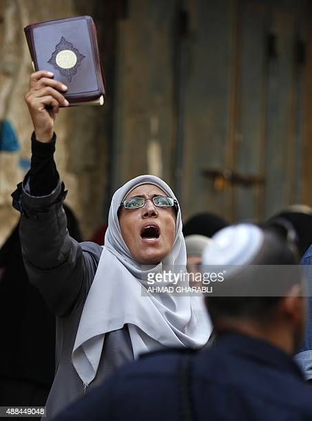 A Palestinian woman from the socalled Murabitat group shouts slogans as she holds a copy of the Koran Islam's holy book during a protest against...