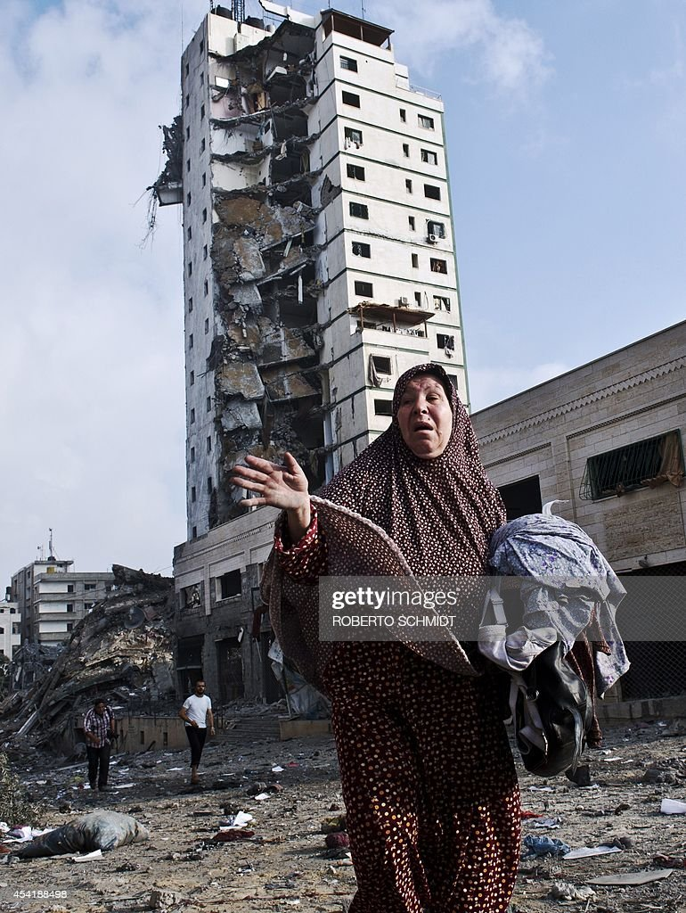 A Palestinian woman gestures as she walks away from her partially destroyed home (not shown) carrying some of her belongings across the street where a high rise apartment building in Gaza City was targeted by Israeli air strikes overnight on August 26, 2014. The residents of the tower were warned to leave the building before the bombing took place. The UN estimates that about a quarter of the 1.8 million inhabitants of Gaza have been displaced by fighting between Hamas militants and Israel.