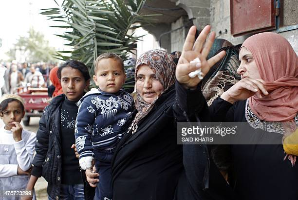 A Palestinian woman gestures as they stand in the street in the town of Khan Younis in the southern Gaza Strip during the funeral procession of Amena...