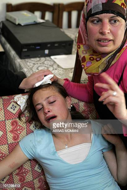 A Palestinian woman gives first aid to a teenager hit on the head by a tear gas canister during clashes following a protest against Israeli...