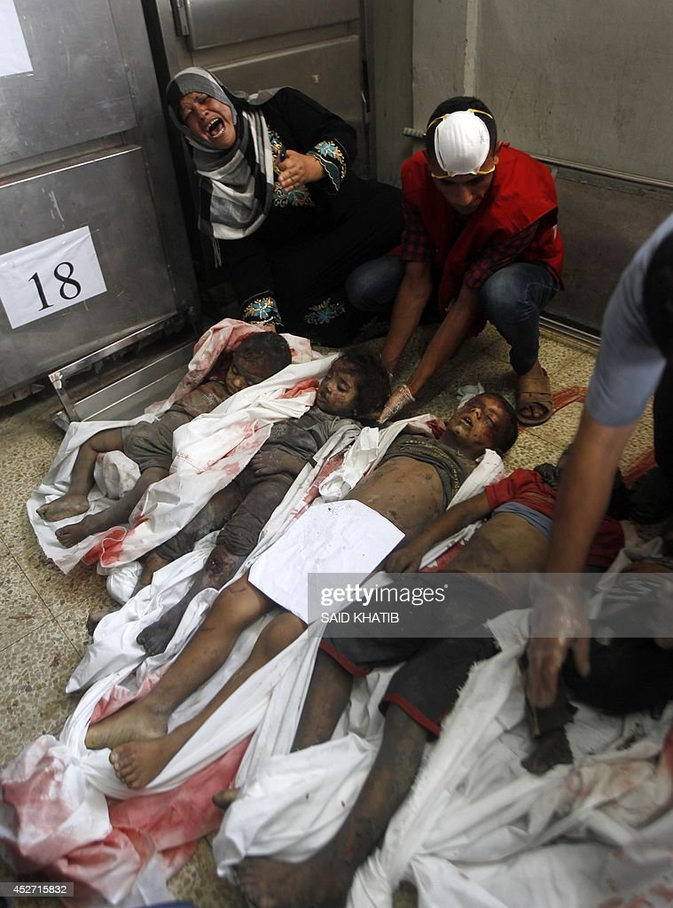 ... at the bodies of Palestinian children from the al-Najjar (Najar)  family, who were killed in an Israeli air strike on their house, at a  hospital morgue ...