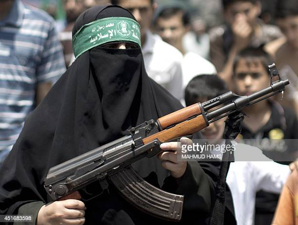 A Palestinian woman Hamas supporter hold up a rifle during a protest against the kidnapping and killing a Palestinian teenager by Israeli settlers in...