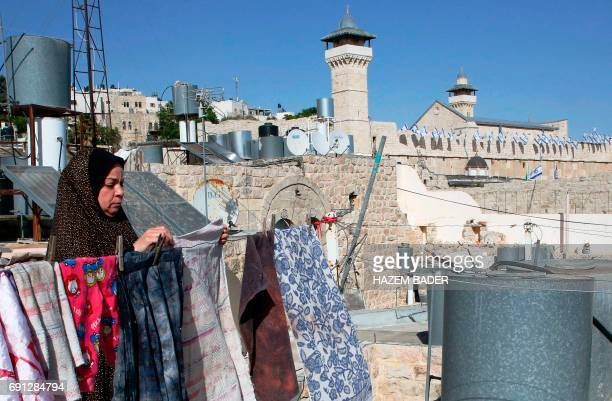 A Palestinian woman hangs clothes on the roof of her house overlooking the old city of the West Bank city of Hebron and the site known to Muslims as...