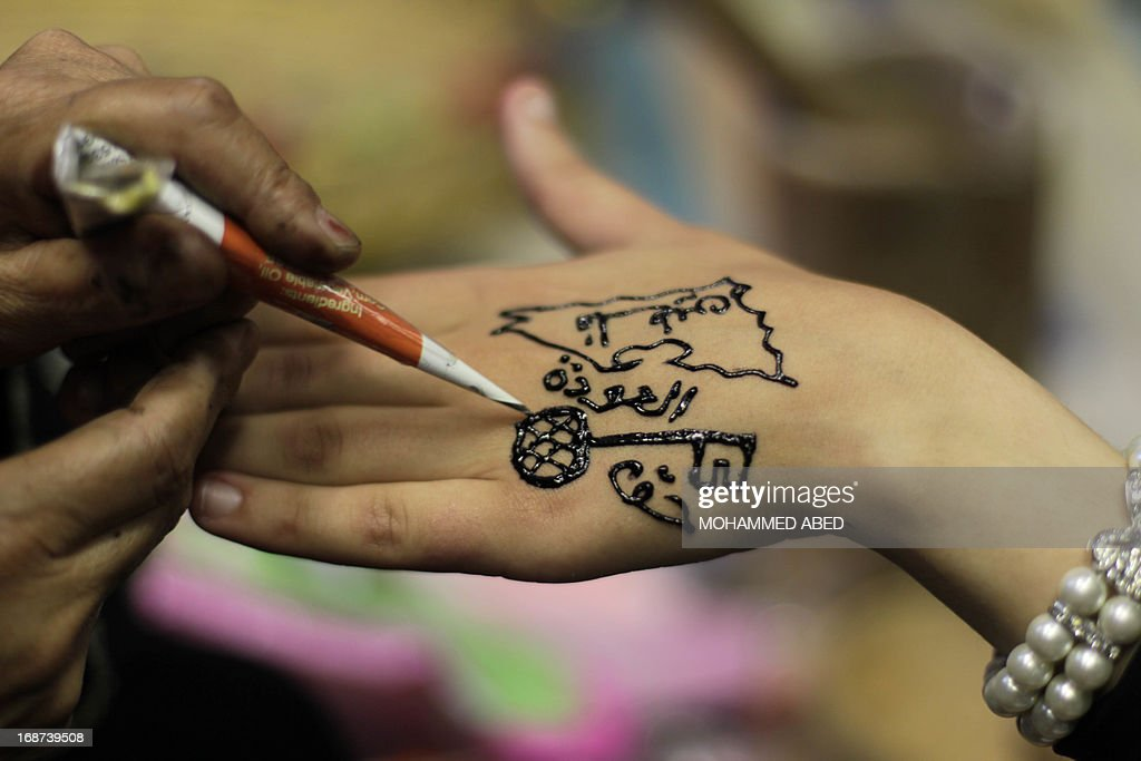 A Palestinian woman has a Nakba (catastrophe) henna tattoo applied on her hand during a rally in Gaza City, on May 14, 2013, as Palestinians start to mark Nakba, or catastrophe in Arabic, which commemorates the exodus of hundreds of thousands of Palestinians after the establishment of Israel state in 1948.