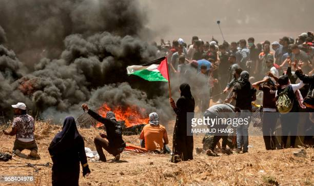 Palestinian woman holding her national flag looks at clashes with Israeli forces near the border between the Gaza strip and Israel east of Gaza City...