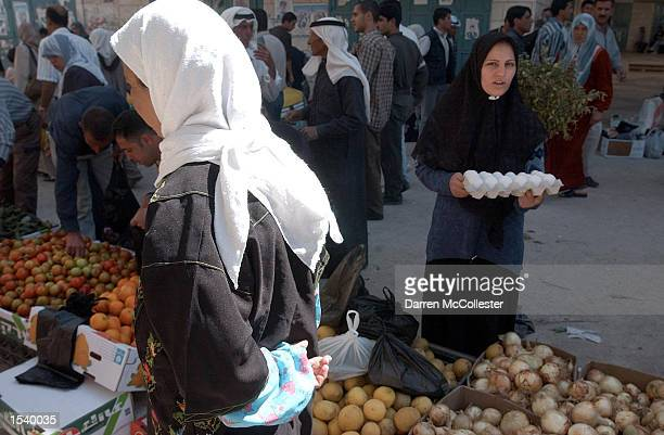 Palestinian woman holds a carton of eggs gathered at the market during the lift of the curfew May 6 2002 in the main square in the West Bank town of...