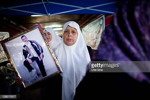A Palestinian woman holds a picture of a relative jailed in Israel during a protest calling for the release of Palestinian prisoners outside the...