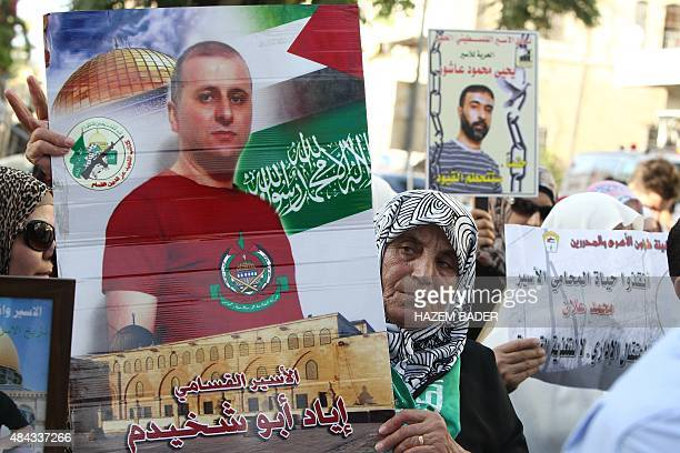 Palestinian woman holds a portrait of a detainee during a demonstration in support of Palestinian prisoners held in Israeli jails, especially...