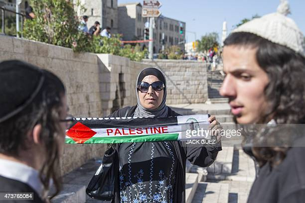 A Palestinian woman holds a scarf bearing the colours of the Palestinian flag as young Israeli nationalists gather outside Damascus Gate in...
