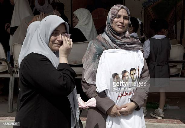 A Palestinian woman holds a Tshirt bearing portraits of the Palestinians who were abducted by gunmen in Egypt's Sinai's northern region during a...