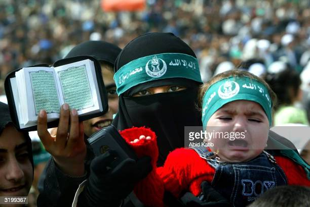 Palestinian woman holds her baby and the Quran as she attends a Hamas rally April 2 2004 at the Jabalya refugee camp in the Gaza Strip Thousands of...