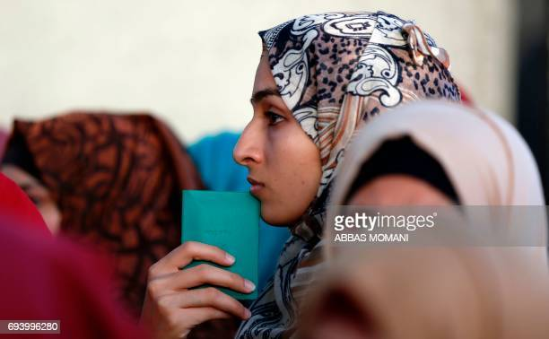 A Palestinian woman holds her identity card as she waits in queue at the Qalandia checkpoint in the occupied West Bank on June 9 in order to attend...