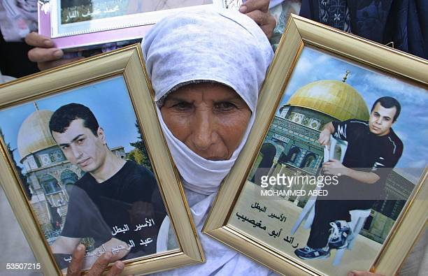 Palestinian woman holds portraits of imprisoned relatives during a rally organized by the Islamic Resistance Movement Hamas in Gaza City to demand...