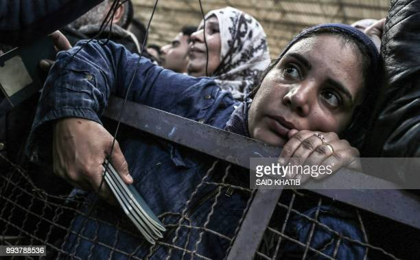 Palestinian woman holds travel documents as she queues in a makeshift station in Khan Younis in the southern Gaza strip on December 16, 2017 as she...