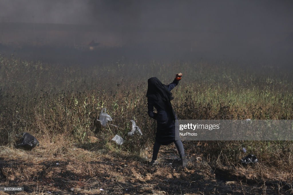 A Palestinian woman hurl stones at Israeli troops during a protest at the Gaza Strip's border with Israel, Friday, April 6, 2018.