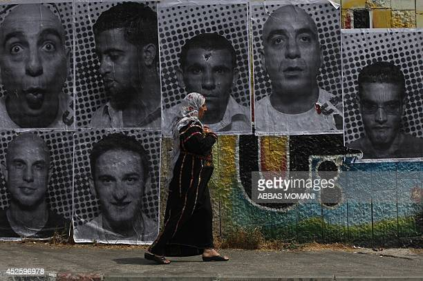 A Palestinian woman in traditional dress walks past large black and white photographs taken by French street artist JR of Palestinians on September 6...
