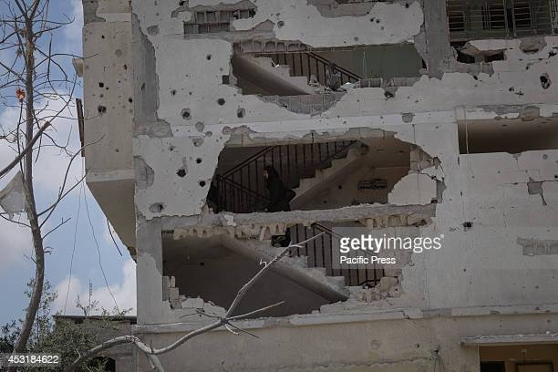 Palestinian woman inspects a destroyed house in Beit Hanoun in the northern Gaza Strip after Israel declared a humanitarian truce to stop the war for...