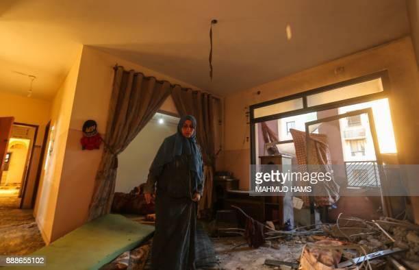 A Palestinian woman inspects the damage at her house on December 9 in the aftermath of an Israeli air strike in Beit Lahia in the northern Gaza Strip...