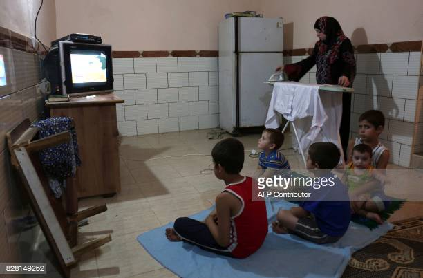 A Palestinian woman irons clothes during the few hours of mains electricity supply they receive every day on July 31 at Rafah refugee camp in the...