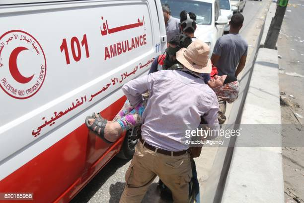 Palestinian woman is affected by Israeli forces' tear gas during a protest against Israeli violations and restrictions on Al Aqsa Mosque at Qalandiya...