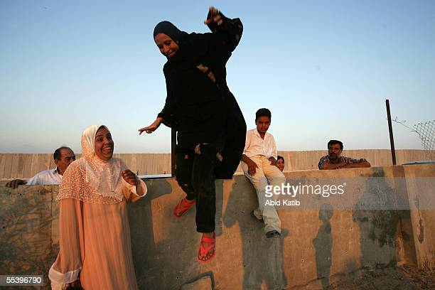 Palestinian woman jumps over the wall to cross the now EgyptianPalestinian controlled border September 13 2005 in Rafah Egypt Thousands of...