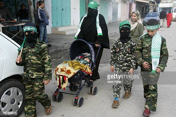 Palestinian woman leads her children as they wear masks camouflage and Hamas headbands as they attend a protest organized by the Hamas movement...